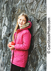 Outdoor vertical portrait of cute 9 year old little girl wearing pink winter coat in a city, holding pomegranate