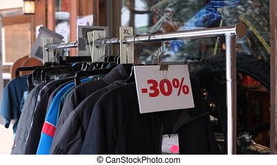 A zooming in video of an outdoor shop, featuring skiing clothes of different sizes and color, a 30 percent sale sign is put on the stand