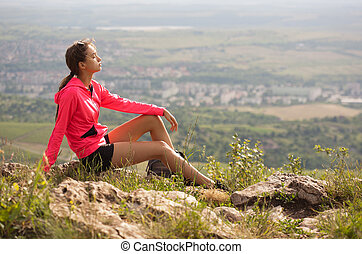 Fit young brunette woman doing outdoors exercise in fresh air.