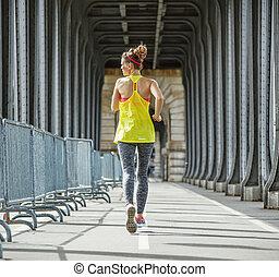 sportswoman jogging on Pont de Bir-Hakeim bridge in Paris -...