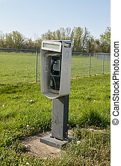 Outdoors freestanding phone booth in a field