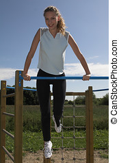 Outdoors gym - Pretty blond woman using the kids playground ...