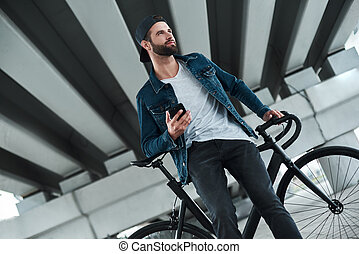 Outdoors leisure. Young stylish man sitting on bycicle on city street holding smartphone looking aside smiling joyful