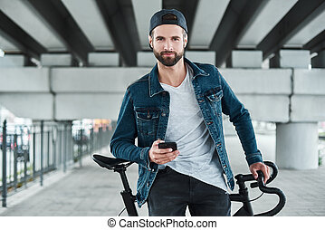 Outdoors leisure. Young stylish man sitting on bycicle on city street holding smartphone looking camera smiling happy
