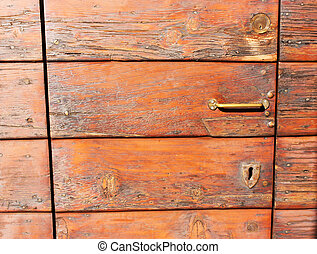 Outdoors  old, antique, wooden door with a keyhole