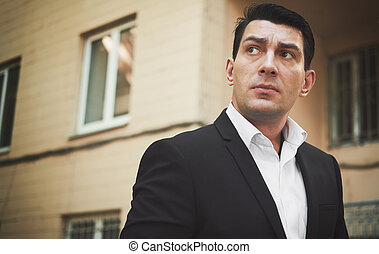 Outdoors portrait of a man in black suit looking up
