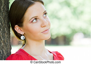 Outdoors portrait of beautiful young brunette woman.