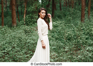 Outdoors portrait of beautiful young caucasian brunette woman in white dress over green foliage on background