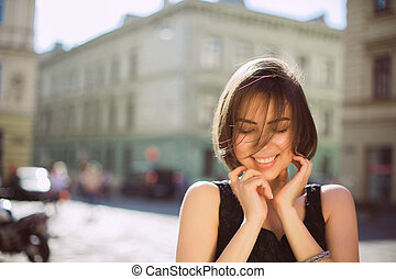 Outdoot portrait of cheerful brunette girl wearing trendy dress, posing on the city streets. Empty space