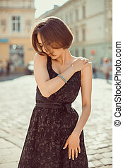 Outdoot portrait of lovely brunette girl wearing trendy dress, posing on the city streets