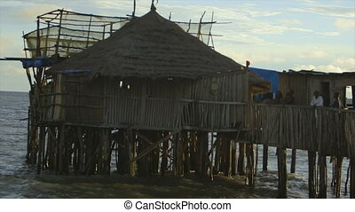 """Close up view of """"Obama Caf?"""", bright cloudy sky, Conakry, above shallow splashing coastal shore water, many wooden pillars supporting the structure above , walking bridge hang, local building materials, thatched roof, raw timber, customers wave"""