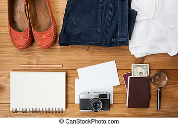 Outfit of traveler, student, teenager, young woman. Overhead of essentials for a person. Different objects on wooden background.