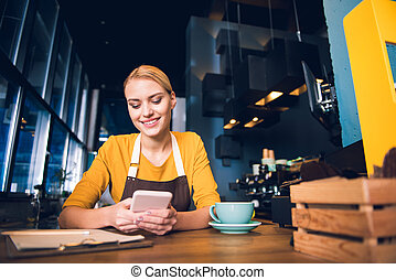 Outgoing female barista typing in phone