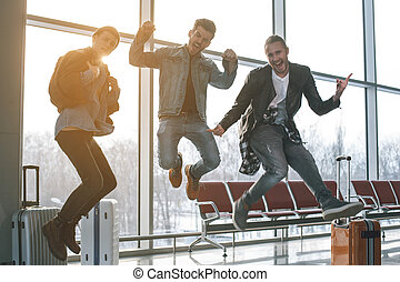 Outgoing friends jumping in airport