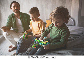 Outgoing kids playing with toys near dad