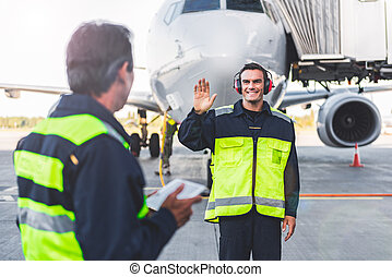 Outgoing mechanic waving hands to colleague