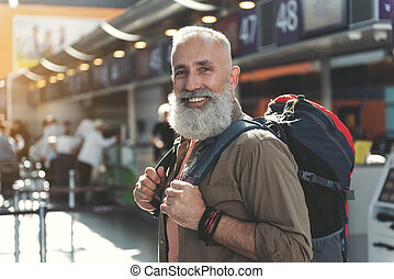 Outgoing unshaven traveler locating in airdrome