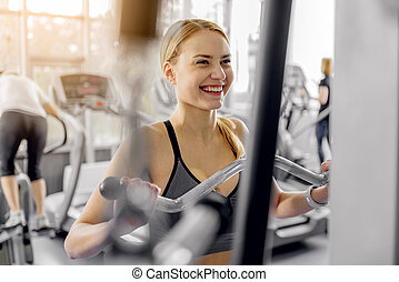 Outgoing woman training with pulldown station - Cheerful...