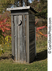 Outhouse with a moon shaped window in the woods