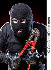Outlaw - a burglar wearing a balaclava holding huge wire ...