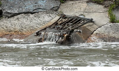 Outlet flows into city river. - Grated outlet flows into...