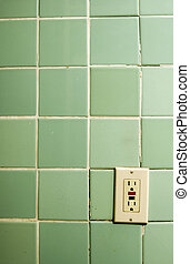 Outlet - old bathroom tiles with heavily used outlet