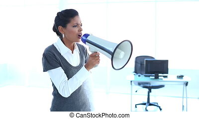 Outraged businesswoman screaming in a megaphone in office