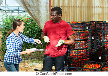 Outraged female farmer and confused worker talking in greenhouse vegetable store