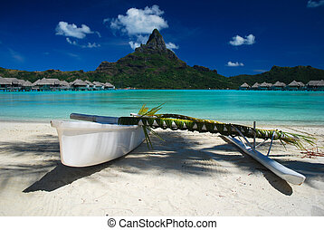 Beautiful shot of a Polynesian outrigger canoe against the Otemanu mountain of Bora Bora
