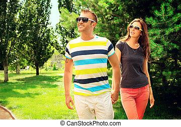outside - Beautiful happy couple walking in the park in...