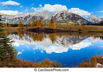 Outskirts of Kenmore. Three Sisters Mountain in Canadian Banff Park. Bright autumn forest is reflected in the smooth water of the lake. The concept of active, ecological and photo tourism