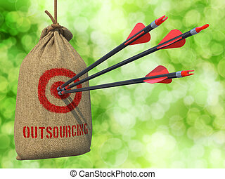 Outsourcing - Three Arrows Hit in Red Target on a Hanging Sack on Green Bokeh Background.