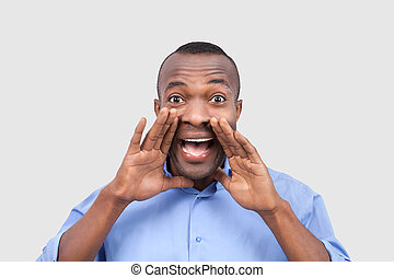 Outstanding news! Handsome African man holding hands near mouth and shouting while isolated on grey
