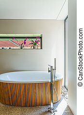 Oval bathtub with wooden enclosure - Simple modern bathroom...