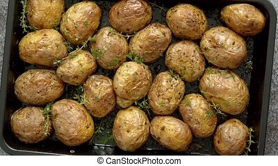 Oven baked whole potatoes with seasoning and herbs in ...