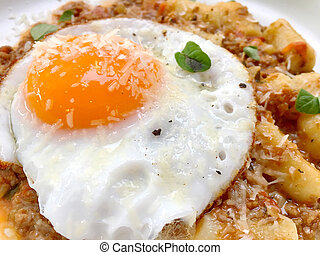 Over easy fried egg with cheese sprinkled on top of Italian ...
