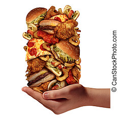 Over eating and compulsive indulgence of fast food concept as a hand holding up a huge stack of junk food as hamburgers hotdogs and french fries as an unhealthy diet nd bad nutrition symbol isolated on a white background.