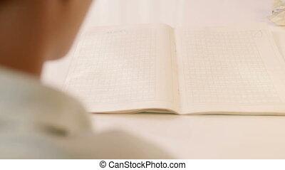 over shoulder close up shot of Asian boy cheering at writing book
