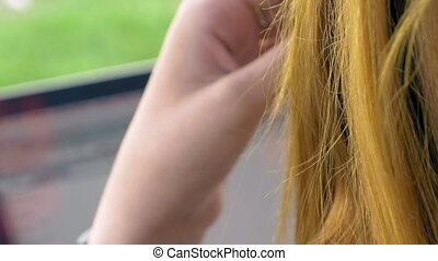 Over shoulder of young woman with red hair - View over...