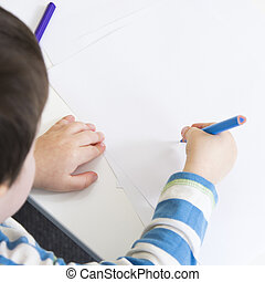 Over shoulder view of a young boy drawing