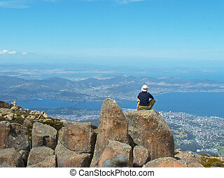 Over the mountains      - A young woman leaning over cities.