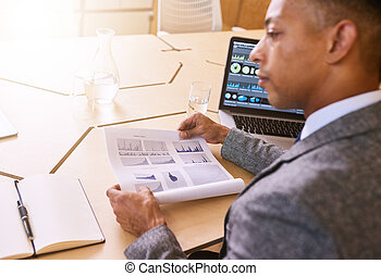 Over the shoulder image of businessman holding document with...