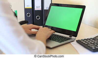 Over the shoulder shot of a woman typing on a laptop with a key-green screen.