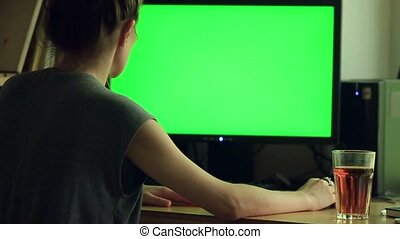 Over the shoulder shot of woman typing on a computer green screen