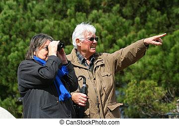 An elderly married couple sightseeing with binoculars