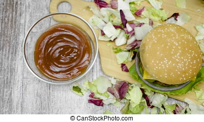 Over top dolly shot of home made hamburger with fries on wooden table