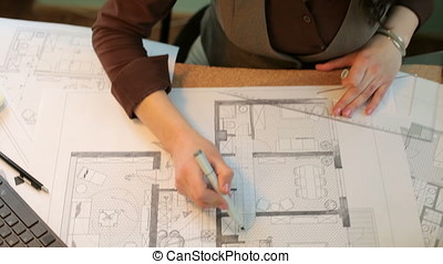 Over top view of architect hands working on blueprints
