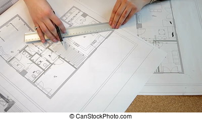 Over top view of architect working on blueprints plan
