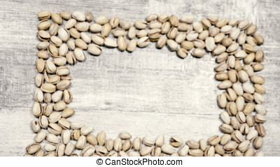 Over top view of Pistachios on wooden background with...