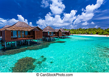 Over water bungalows with steps into green coral lagoon -...